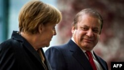 German Chancellor Angela Merkel (L) and Pakistani Prime Minister Nawaz Sharif chat as they review a military guard of honor at a welcoming ceremony at the Chancellery in Berlin on November 11, 2014.