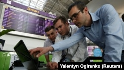 Technicians work on a flight timetable for the website of Ukraine's Boryspil Airport near Kyiv following a cyberattack on June 27 that started in Ukraine before spreading elsewhere.