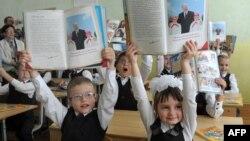 Belarus -- Pupils hold books about President Alyaksandr Lukashenka at a school in Minsk, September 1, 2012