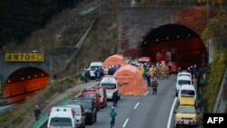 Rescue workers and police gather outside the Sasago Tunnel after part of the tunnel collapsed.