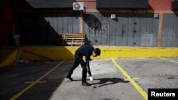 A criminal investigator looks for evidence in a building after an explosion in Caracas, Venezuela