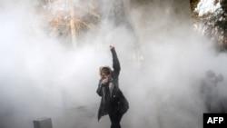 یک زن معترض در میان دود ناشی از گاز اشکآور در مقابل دانشگاه تهران