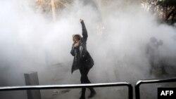 Жінка на території Тегеранського університету намагається врятуватися від дії сльозогінного газу, Іран, 30 грудня 2017 року
