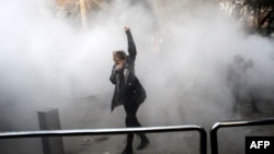 An Iranian woman raises her fist amid the smoke of tear gas at the University of Tehran during a protest driven by anger over economic problems in the capital on December 30.