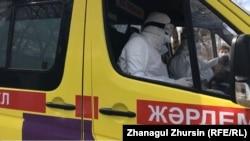 Медики в защитных костюмах в машине скорой помощи.