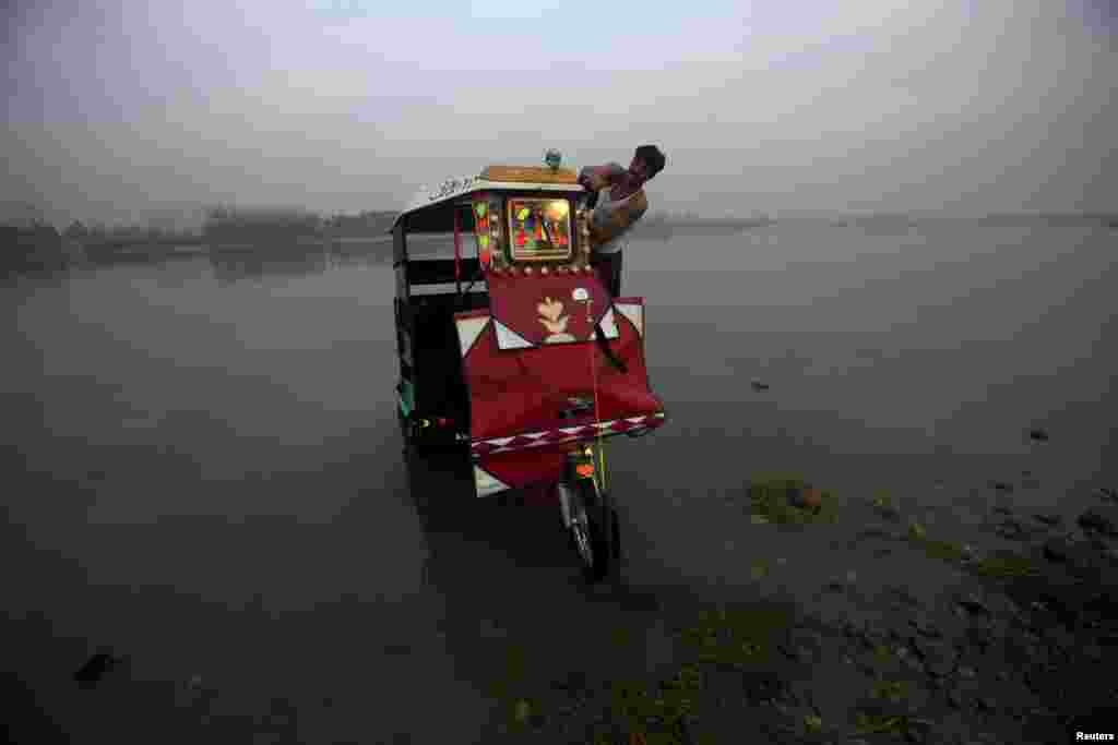 A man washes his rickshaw on the shores of the Sardaryab River in Charsadda near Peshawar, Pakistan, on December 4. (Reuters/​Fayaz Aziz)