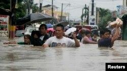 Banorët e qytezës Kawit, në jug të Manilës ecin në një rrugë të përmbytur nga të reshurat që e kanë goditur Filipinet, 19 gusht 2013