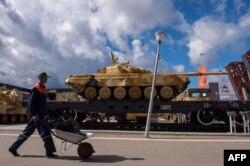 Рабочий идет мимо платформы с танком. Поселок Кубинка Московской области, 8 сентября 2016 года.