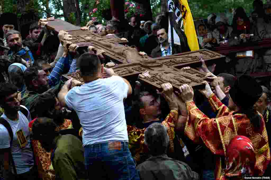 Marchers with a carved cross at the site where investigators discovered the bodies of Russia's last royal family.