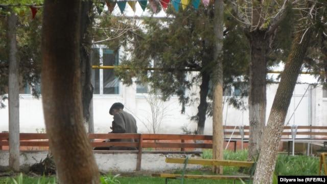 Шымкенттегі жазасын өтеп шыққан азаматтарға арналған әлеуметтік бейімдеу орталығының ауласында отырған адам. 14 наурыз 2016 жыл.