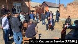 Ахмед Погоров сидит в центре, обращаясь к собравшимся после задержания участника протестов Ибрагима Дугиева в Ингушетии
