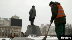 Работники коммунальных служб вычищают последствия взрыва возле памятника Ленину в Донецке. В результате взрыва, произошедшего 27 января, была повреждена часть постамента