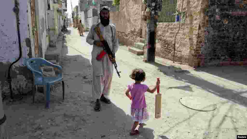 OCTOBER 24, 2012 -- A girl with a cricket bat walks past a bodyguard of the leader of the the highly secretive Sunni Muslim extremist group Lashkar-e Jhangvi holding a rifle on a street near Malik Ishaq's home in Rahim Yar Khan in Pakistan's southern Punjab Province. (Reuters/Mian Khursheed)