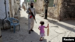 A girl with a cricket bat walks past a militant in Rahim Yar Khan, southern Punjab Province (file photo)