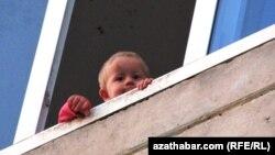Балконнан қарап тұрған бала. Көрнекі сурет.