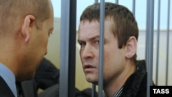 Jailed opposition activist Leonid Razvozzhayev (right) in a Moscow court on March 29