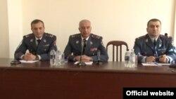 Armenia -- Deputy Police Chief Anubagh Hambaryan (C) presents the newly appointed Chief of the Passport and Visa Department Mnatsakan Bichakhchian (L), 21 Oct, 2015