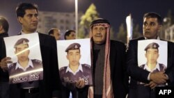 أقارب الطيار الأردني معاذ الكساسبة وهم يحملون صوره التي كُتب عليها (كلنا معاذ)