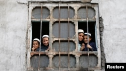 Afghan students from a religious school look on from a window of their school in Kabul on October 5.