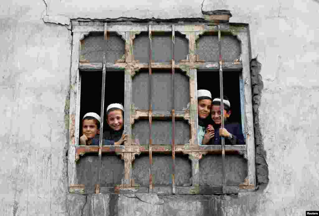 Afghan students look out a window at their religious school in Kabul.(Reuters/Omar Sobhani)