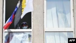 Пророссийский боевик в захваченном здании СБУ, Луганск, апрель 2014 года