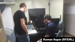 Джон Хен Му показывает студию Роману Суперу.