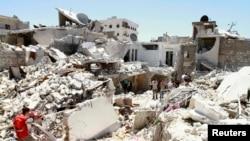 شام: په حلب کې د بشار الاسد پلوه ځواکونو په هوايي برید کې کنډکپرې ودانۍ. ۲۷ جولای ۲۰۱۳