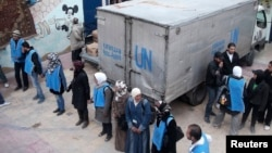 Сотрудники агентства ООН помощи беженцам и организации работ стоят у грузовика с гуманитарной помощью в лагере для палестинских беженцев Ярмук недалеко от Дамаска. 26 февраля 2014 года.