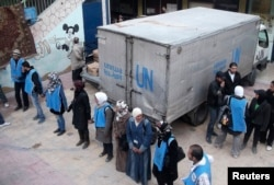 UN Relief and Works Agency (UNRWA) workers stand by aid parcels at the Yarmouk camp in February 2014. The UNRWA says it now has limited access to the camp