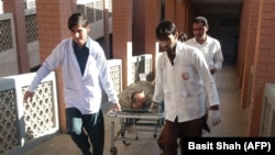 Pakistani paramedics carry an injured bomb blast victim to a hospital after the bombing at a market in the northwestern district of Orakzai.