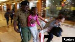 Солдат кенийской армии выносит ребенка в укрытие после захвата заложников в Найроби.
