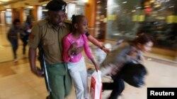 """Полицейский выводит людей, взятых в заложники группировкой """"Аль-Шабаб"""" в торговом центре Westgate. Найроби, 21 сентября 2013 года."""