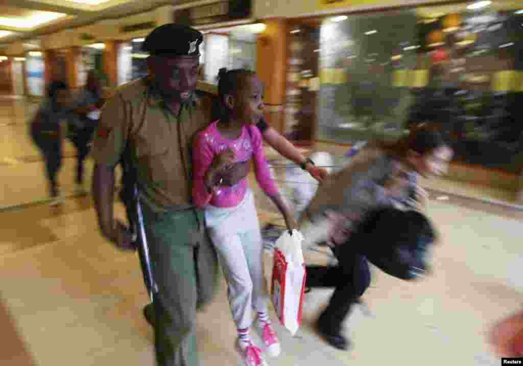 A Kenyan soldier carries a child to safety as armed police hunt Islamist extremists who went on a shooting spree at the Westgate shopping center in Nairobi. (Reuters/Goran Tomasevic)