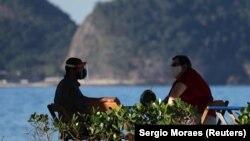 Посетители бара на пляже Копакабана в Бразилии.