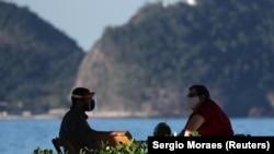 COVID-19 ýaýraýan wagty Rio-de-Žaneýronyň Kopakabana plýažynyň kenarynda oturan iki adam