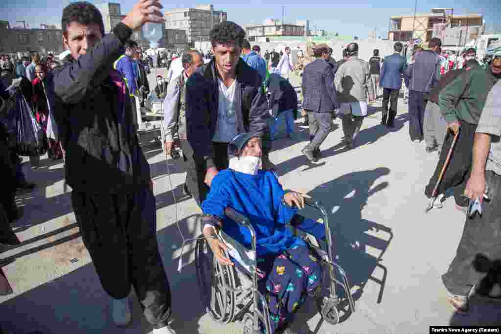 Men tend to an injured woman in Sarpol-e Zahab.