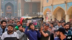 Mourners carry the coffin of Mehdi Kadim, 17, a protester killed during anti-government demonstrations, during his funeral in Najaf, Iraq, Friday, Nov. 29, 2019.(AP Photo/Anmar Khalil)