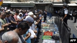 Palestinian Muslim worshippers pray outside Damascus Gate in Jerusalem's Old City on July 21.