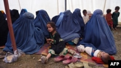 Afghan women sit with their children after returning to Afghanistan from Pakistan in September 2016.|