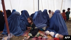 Afghan refugees sit with their children after returning to Afghanistan from Pakistan in a camp on the outskirts of Kabul. (file photo)