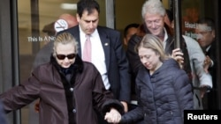 U.S. Secretary of State Hillary Clinton (left) leaves New York Presbyterian Hospital with husband Bill (top right) and daughter Chelsea (right) in New York on January 2.
