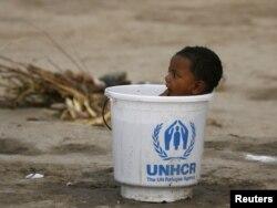БҰҰ-ның босқындар ісі басқармасы әкелген ауызсудың босаған шелегінде отырған бала. Пәкістан, 30 тамыз 2010 жыл.