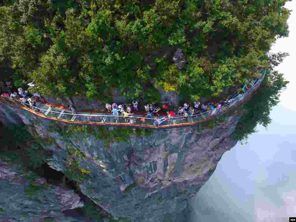 An aerial view of tourists walking on a glass-bottomed skywalk on the Panlong Cliff on Tianmen Mountain in Zhangjiajie, Hunan Province, China. The 100-meter-long walk, giving a clear view of the deep valley 1,400 meters below, is the third glass walkway in the scenic zone. (epa/Shao Ying)
