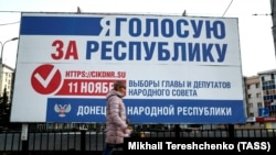 A woman walks past an election campaign billboard on a street in Donetsk on November 7.