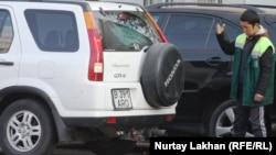 Работник автостоянки помогает автовладельцу припарковаться. Алматы, 6 ноября 2013 года.