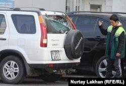 Алматыдағы жол жиегіндегі автотұрақтардың бірінің бақылаушысы. (Көрнекі сурет)