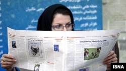 Iran -- Tehran, An Iranian woman reads a newspaper in 15th press festival in Tehran.