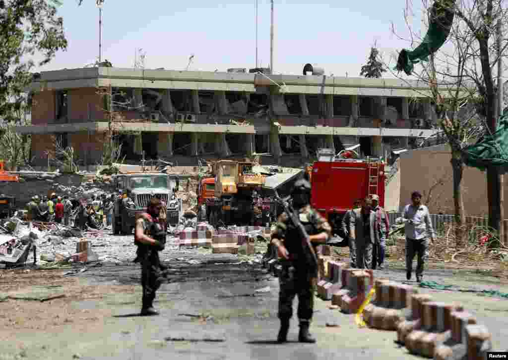 Afghan officials inspect outside the damaged German Embassy.