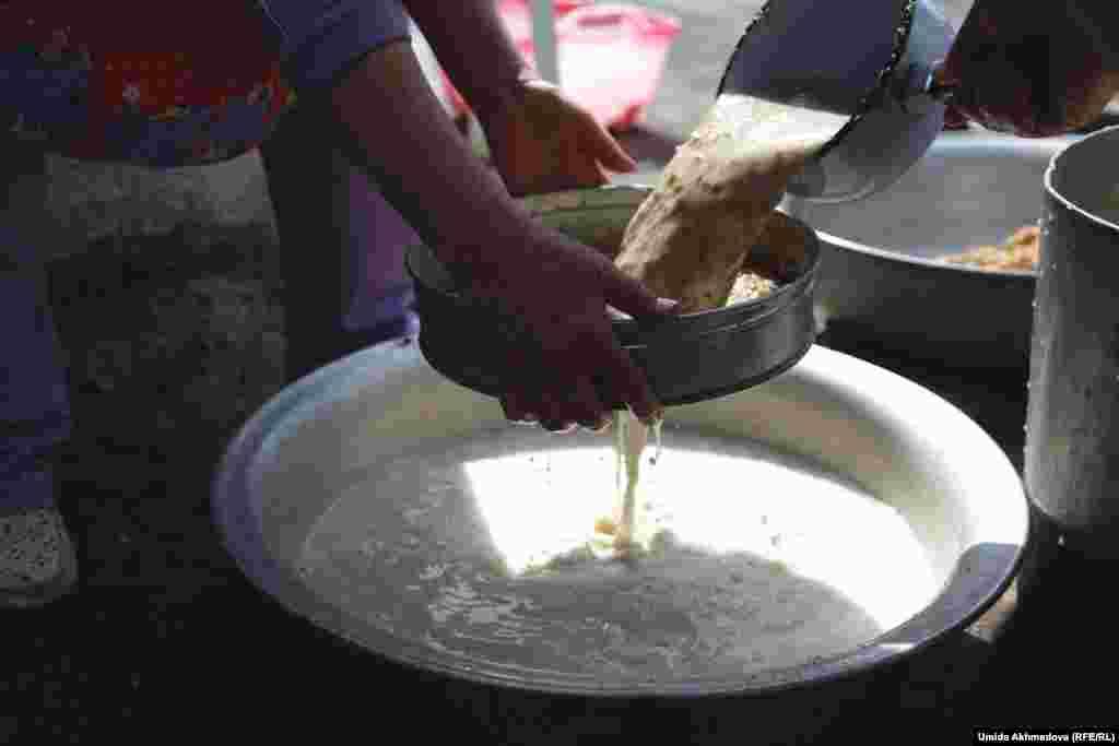 Жергілікті әйел түйген бидайды сүзіп, сумаляк атты дәстүрлі тағам пісіруге дайындалып жатыр.