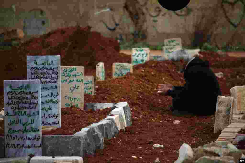 A Syrian man mourns at the graves of relatives in a rebel-held area of the city of Daraa in southern Syria. (AFP/Mohamad Abazeeed)